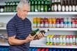 Senior Man Comparing Beer Bottles