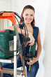 Portrait of beautiful  woman in overalls with drill
