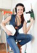 woman in headphones with drill and hardhat