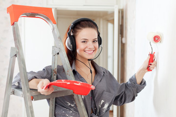 Happy  woman in headphones paints wall
