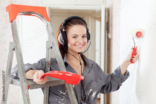 Happy  woman in headphones paints wall