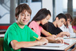 Boy Sitting At Desk With Friends Writing In Classroom