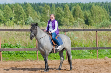 Beautiful smiling girl riding a gray horse