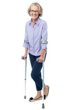 Bespectacled old woman walking with crutches