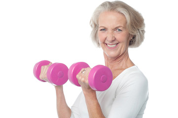 Joyous fit woman lifting dumbbells