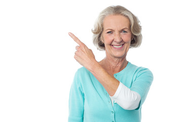 Pretty aged woman pointing at something