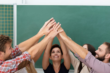 lachende studenten halten hände zusammen nach oben
