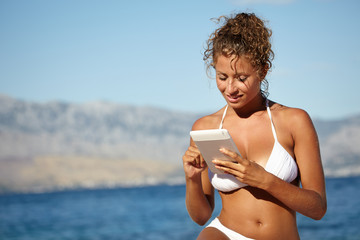 woman using electronic tablet at the beach