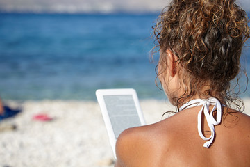 Woman with an e-reader on vacation at the beach reading a book.
