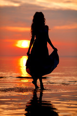 Happy Woman enjoying in Sea Sunset. Silhouetted against the suns