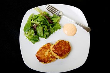 Two Crab Cakes and Salad on Black Background