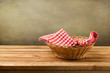 Empty basket with checked tablecloth on wooden table