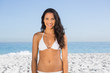 Smiling pretty long haired woman in white bikini posing
