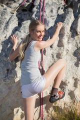 Rear view of blonde woman climbing