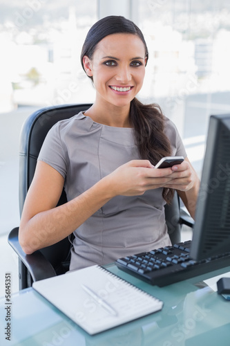 Cheerful gorgeous businesswoman texting on her smartphone