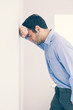 Devastated man leaning his head against a wall