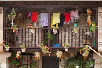Ropa colgada en balcón con mazorcas