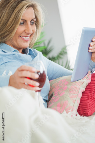 Smiling woman lying on a sofa drinking wine and using a tablet p