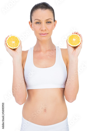 Cheerful slender woman in sportswear holding slices of orange