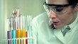 Female scientist examine test tubes in laboratory