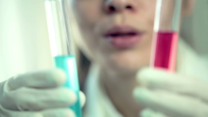Female scientist comparing test tubes with colorful substance
