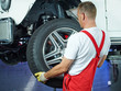 Car mechanic changes car tyres in a garage