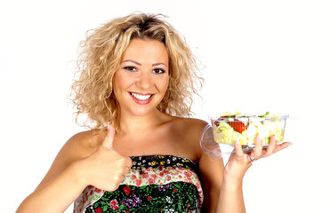 Schöne lachende junge Frau mit Salat in der Hand und Daumen hoch
