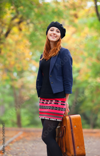 Redhead girl with suitcase at autumn outdoor.