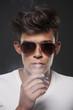 Fashionable young man exhaling cigarette smoke