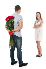 Loving couple. Full length of handsome man holding bunch of flow