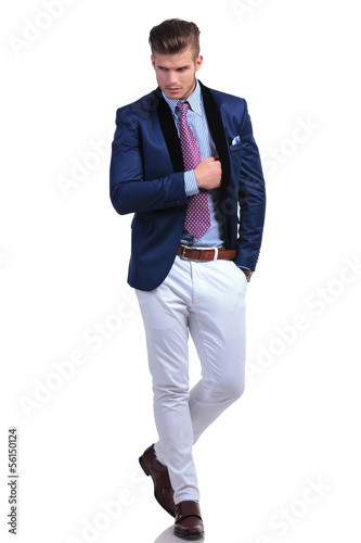 young business man walks and inserts hand in jacket