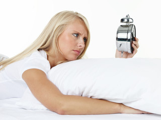 Woman with alarm clock awakes in the morning