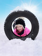 Cute girl with snowy winter tyre in front of blue sky
