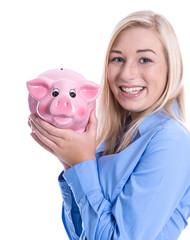 Junges Mädchen isoliert in blauer Bluse lachend mit Sparschwein