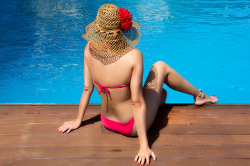 Beauty Woman Sitting on edge of Swimming Pool