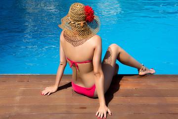 Beauty Woman Sitting on edge of Swimming Pool