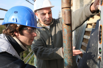 Builder's apprentice being shown how to operate machinery