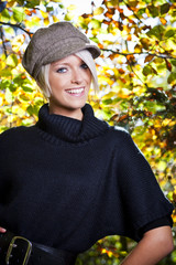 Stylish beautiful woman in autumn foliage