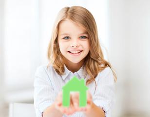 girl holding green paper house