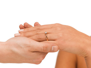 man puts wedding ring on woman hand