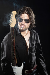 Rock guitarist with long brown hair and beard and sunglasses dre