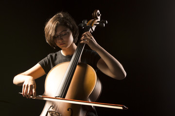 Young cellist isolated on black