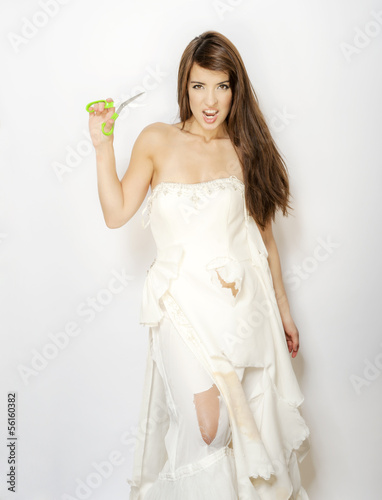 sexy woman in ripped and cut wedding dress holding scissors