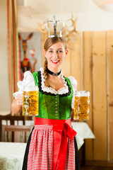 Young woman as queen in Bavarian restaurant