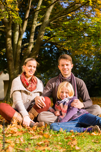Happy Family outdoors sitting on grass in autumn