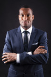 Portrait of a confident young black business man on dark backgro