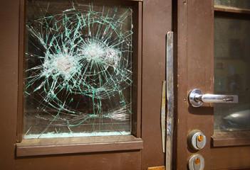 Broken window on  door by vandalism