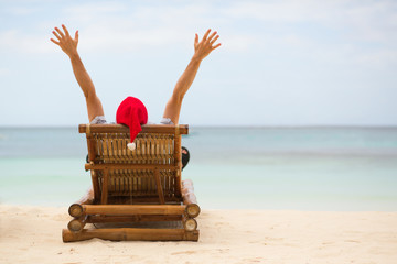 Santa sitting on chaise longue on white sand beach