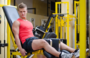 Handsome young man working out on gym equipment