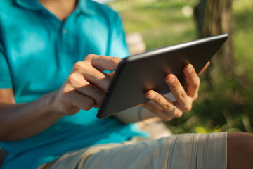Man using a digital tablet outdoors